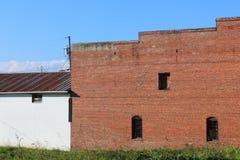 Voorgevel van de oude baksteenbouw en de witte bouw tegen een blauwe hemel Stock Afbeelding