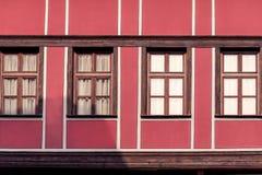 Voorgevel van de oude, rode, historische bouw met vier vensters Stock Afbeeldingen