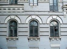 Voorgevel van de oude verlaten bouw met drie grote overspannen vensters stock afbeeldingen