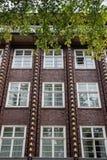Voorgevel van de rode baksteenbouw met gouden Ornamenten en witte Vensters, Hamburg, Duitsland Stock Foto