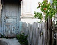 Voorgevel van een oud huis met grijs-blauwe deuren en omheining Stock Fotografie