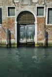Voorgevel van gedeeltelijk bemost oud baksteenhuis met houten uitstekende deur stock afbeelding