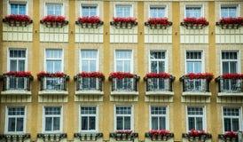 Voorgevel van het hotel met vensters op een rij en balkons met bloemen worden verfraaid die Stock Afbeelding