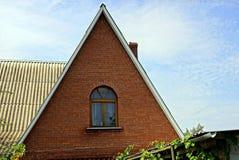 Voorgevel van het huis van baksteen bruine zolder met een venster tegen de hemel royalty-vrije stock afbeeldingen