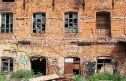 Voorgevel van het oude rode baksteengebouw met gebroken vensters en sporen van vandalisme Stock Foto's