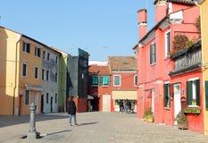 Voorgevels van kleurrijke gebouwen en toeristen die in de stad van Burano, Italië lopen stock fotografie