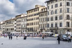 Voorgevels van Renaissancehuizen in het Santa Maria Novella-vierkant, met terrassen van bars en vele mensen het wandelen stock afbeelding