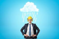 Voorgewassenbeeld die van zakenman in gele bouwvakker met oorverdedigers, zich met handen op heupen onder het witte regenen bevin stock afbeeldingen