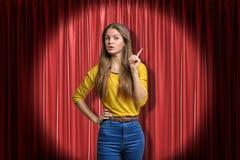 Voorgewassenmening die van mooi jong meisje in gele verbindingsdraad en jeans, zich in schijnwerper tegen rood stadiumgordijn bev stock fotografie