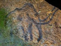 Voorhistorische kunst van mammoet in zandsteenhol De schijnwerper glanst bij het historische schilderen Stock Foto's