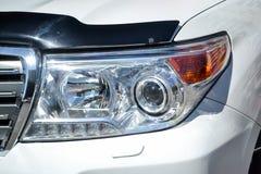 Voorkoplampmening van auto in witte kleur na het schoonmaken en het detailleren met wasmachine v??r verkoop Grote lamp op voertui royalty-vrije stock afbeelding