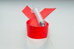 Voorlichtings rode lint en spuit op witte achtergrond: werelddag tegen AIDS, de bevordering van overheidssteun voor Stock Afbeelding