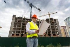 Voorman die op blauwdrukken bouwterrein bekijken Royalty-vrije Stock Fotografie