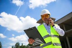Voorman in eenvormig werken expertising de structuur die zich met omslag bij de bouwwerf bevinden royalty-vrije stock afbeelding