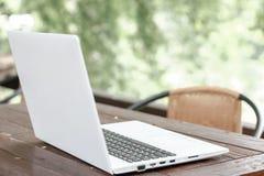 Voorraadfoto: Computerlaptop op houten lijst met onduidelijk beeldaard B royalty-vrije stock afbeeldingen