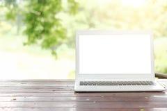 Voorraadfoto: Computerlaptop op houten lijst met onduidelijk beeldaard B stock afbeelding