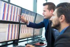 Voorraadhandelaren die de computerschermen bekijken Stock Afbeelding