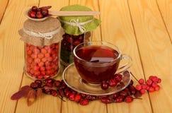 Voorraden van bessen in kruiken, kop thee, tegen de achtergrond van lijst royalty-vrije stock fotografie