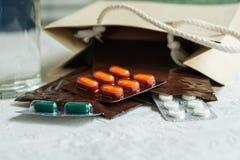 Voorschriftorde van het ziekenhuis arts met geneesmiddelen, drug in plastic pitzakken voor chronische patiënt met glas water op w royalty-vrije stock fotografie