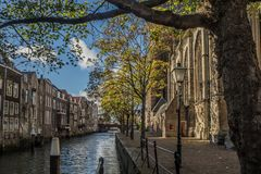 Voorstraatshaven and Grote Kerk in Dordrecht, Netherlands on a sunny afternoon. The trees have autumn colors and the sky is blue with clouds Royalty Free Stock Image