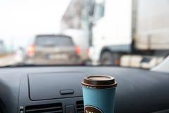 Voorvenstermening van binnenuit een auto met een lege koffiekop in de avond opstopping royalty-vrije stock fotografie