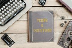 Voorwaarden op oude boekdekking bij bureau met vinta Stock Fotografie
