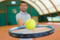 Voorwaartse het tennisbal van de mensenholding op racket Royalty-vrije Stock Afbeelding