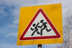 Voorzichtigheidskinderen die verkeersteken kruisen Stock Afbeelding