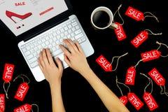 Voorzien de vrouwen vrouwelijke volwassen handen met laptop kopende het kopen nieuwe rode hoge hielen met verkoop in Internet onl stock foto's