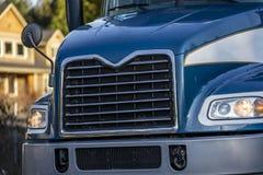 Voorzijde van donkerblauwe grote installatie semi vrachtwagen met chroomtraliewerk en koplamp stock foto