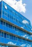 Voorzijde van een modern gebouw De glasvensters wezen op de hemel en de wolken blauwe gamma Royalty-vrije Stock Afbeelding