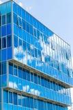 Voorzijde van een modern gebouw De glasvensters wezen op de hemel en de wolken blauwe gamma Stock Foto