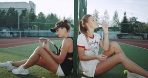 Vor dem Beginnen große haben Berufsspielerdamen des Tennisplatzes zwei eine Abschaltzeit, das Trinkwasser des Tennis zu spielen u stock footage