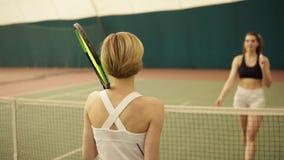 Vor dem Beginnen zwei weibliche Konkurrenten rütteln jede andere Hände, Tennis spielend stock video