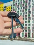 Vor dem hintergrund eines modernen Wohngebäudes Hand mit Schlüsseln zur Wohnung lizenzfreie stockbilder