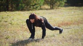 Vor der Ausbildung in der Natur eine junge Frau in einer Klage wärmt ihre Beinmuskeln stock video footage