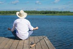 Vor der Fischerei ein Mann meditiert auf dem Pier, vor dem hintergrund des Wassers und des Himmels, stockfotografie