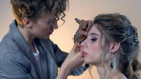 Vor der Heirat Maskenbildner und Friseur bereiten Braut vor Friseur-Stilist mit kurzer stilvoller Frisur wendet Make-up an stock footage
