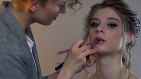 Vor der Heirat Maskenbildner und Friseur bereiten Braut vor Friseur-Stilist mit kurzer stilvoller Frisur wendet Make-up an stock video footage