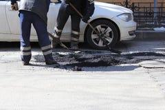 Vor der Pflasterung mit einer Straßenminigebäuderolle zwei Arbeitskräfte planieren die Krume des Asphalts in der Grube mit einer  lizenzfreie stockfotos