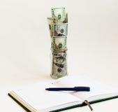 Vor einem offenen Tagebuch mit einem Stift ist ein Glasgefäß mit Dollarscheinen Stockbilder