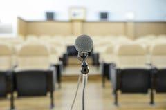 Vor einer Konferenz die Mikrophone vor leeren Stühlen Lizenzfreies Stockfoto