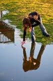 Vor-gießen Sie Mädchen bildet Kräuselung im Wasser mit der Hand aus stockbild