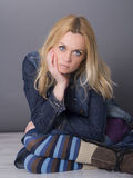 Blonde Frau, die auf dem Boden sitzt Lizenzfreie Stockfotos