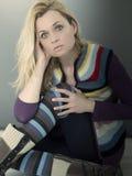 Blonde Frau, die auf dem Boden sitzt Stockfotografie