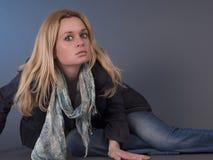 Blonde Frau, die auf dem Boden aufwirft Stockfotos