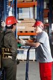 Vorarbeiter Communicating With Coworker am Lager lizenzfreie stockfotos