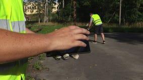 Vorarbeiter, der Tablette nahe Arbeitskraft die unter Verwendung der Bürste verwendet stock footage