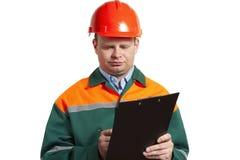 Vorarbeiter in der Uniform schreibt in ein Papiernotizbuch Stockbilder