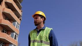 Vorarbeiter in einem gelben Sturzhelm mit einem Bart und einem Schnurrbart geht nahe dem Haus im Bau und spricht über das Bau pro stock video footage